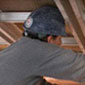 Two construction workers replace cooper roofing (Click to view enlarged image.)