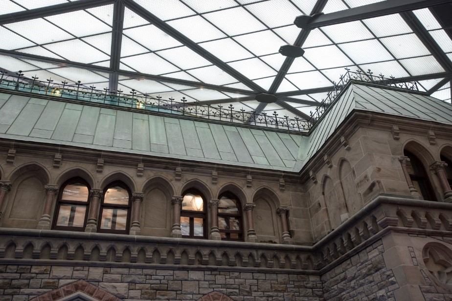 View enlarged image of the façade of a heritage stone building with a green copper roof. Above the façade is a glass roof.