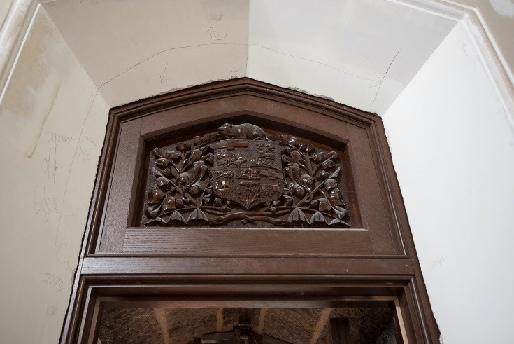 View enlarged image of a wood carving of a coat of arms above a doorway.