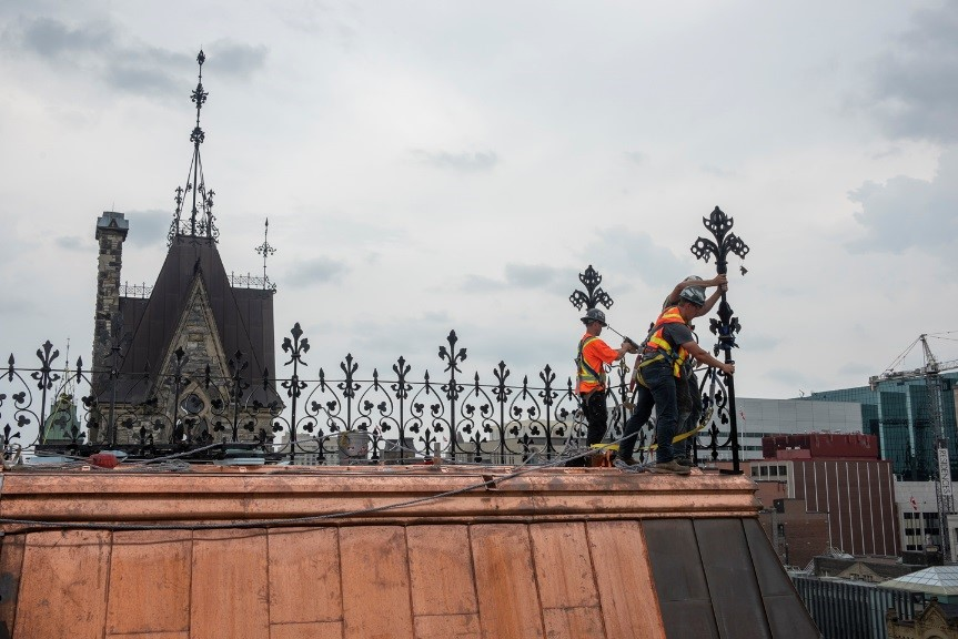 View enlarged image of three workers install ornate iron cresting on a copper roof.