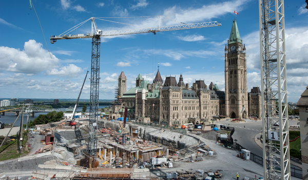 View enlarged image of the construction of Phase 1 of the Visitor's Welcome Centre, with the Ottawa River, the Centre Block and the Peace Tower in the background.