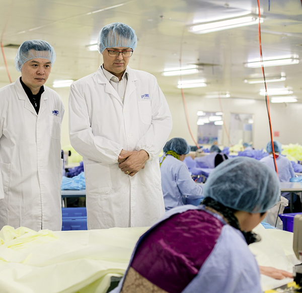 Two men are both wearing white lab coats and blue hair nets. They are standing and watching a woman wearing a blue hair net and protective gown work on the production of face masks.