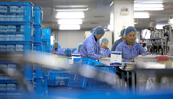 Six people are dressed in blue gowns and hair nets and working on the production of PPE. In the foreground are stacks of blue plastic boxes.